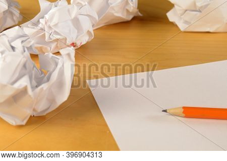 A Blank Page From A Writer Who Has Had Several Page Ideas Crumpled To Throw Away.