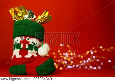 New Year And Christmas Card On A Red Background. Boot With Sweets And Christmas Lights. Content For