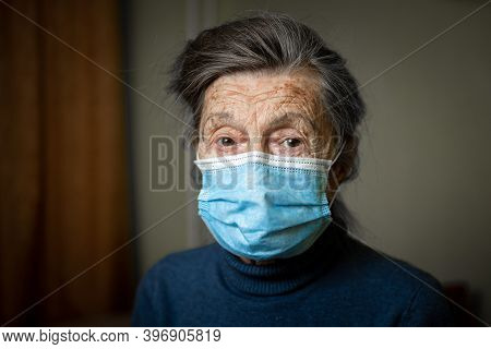 Elderly Caucasian Woman With Wrinkles On Face, Gray Hair, Wearing Medical Mask, Looks Attentively At