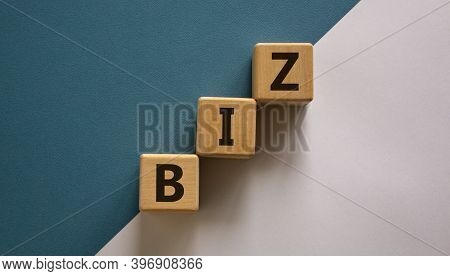 Business Concept Success Process. Wooden Block With A Word 'biz' Stacking As Step Stair On Paper Blu