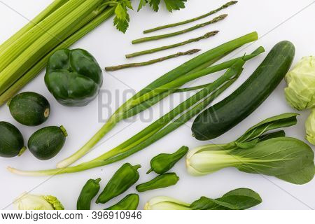Celery, cucumber, spring onion and peppers on white background. fresh produce green vegetables healthy eating organic food preparation concept.
