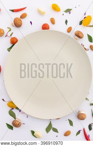 White plate surrounded by fresh vegetables on white background. fresh produce green vegetables healthy eating organic food preparation concept.