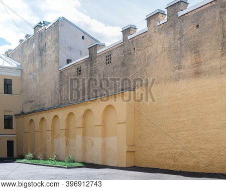 A Beige Wall With Elements In The Form Of Arches In The Courtyard Of The House. On Top Of The Wall,