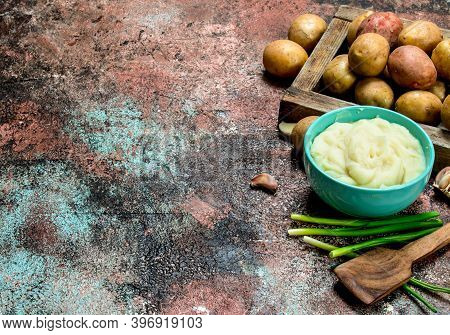 Mashed Potatoes In A Bowl With Green Onions . On A Rustic Background.