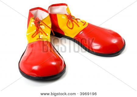 A pair of over sized red and yellow clown shoes on a white background poster