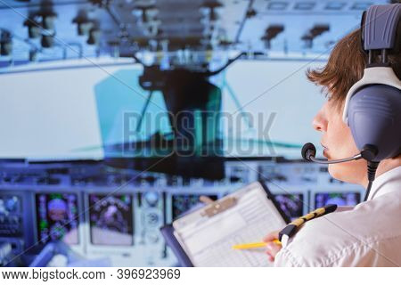 Beautiful woman pilot wearing uniform with epauletes and headset, writting on notepad inside airliner