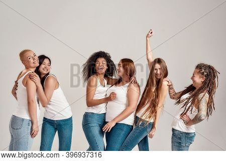 Group Of Six Beautiful Diverse Young Women Wearing White Shirt And Denim Jeans Having Fun, Laughing