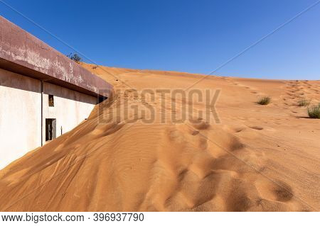Old Residential Building Buried In Sand Dune On A Desert In Al Madam Ghost Village In Sharjah, Unite