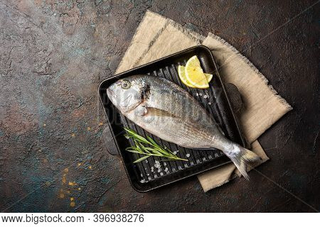 Fresh Fish Dorada Or Gilt-head Bream On Grill Pan With Spices, Kitchen Herb And Lemon