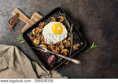Fried Egg And Mushrooms On Grill Pan With Onion, Rosemary