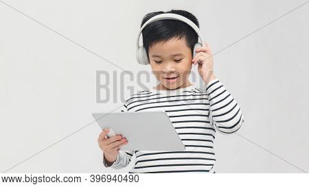 Boy With Electronic Pad And Phones. Isolated On White