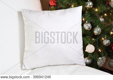 Square White Throw Pillow Napping Lazily On A White Couch. A Festive Lit Up Christmas Tree Adds Holi