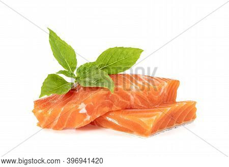 Piece Of Fresh Salmon Fillet Sliced With Leaf Basil Isolated On White Background