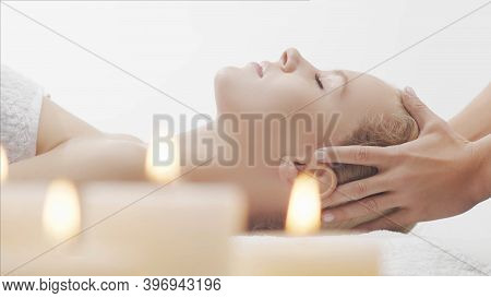 Young, Beautiful And Healthy Woman In Massaging Salon. Traditional Face Massage Therapy And Skin Car