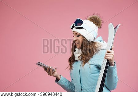Young Woman With Skis Uses A Smartphone To Plan Her Ski Runs. Winter Holidays At A Ski Resort. Woman