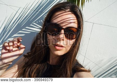 Young Female Tourist In Sunglasses, Summer By The Sea. Portrait Under A Palm Tree, Shadow On The Fac