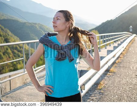 Young Woman After A Morning Jog, Portrait Against The Background Of Mountains