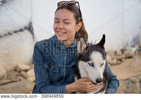 Young Woman And Husky Dog, Stroke A Furry Pet. Care For The Animals