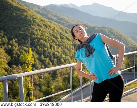 Warm Up In The Morning In The Mountains. Young Woman Doing Exercise, Morning Jog And Healthy Lifesty