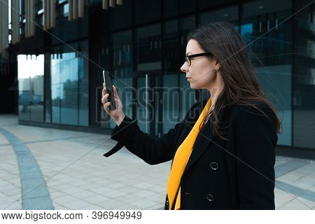 Young Woman Wearing A Coat And Glasses Uses A Smartphone, Taking Photos And Facial Recognition With