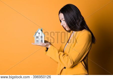 Dream Of Buying A House, Concept. A Young Woman With A House In The Palm Of Her Hand On A Bright Yel