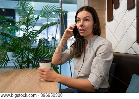 Young Woman Sits At A Table In A Cafe And Communicates On The Internet In Mobile Apps, Smartphone An