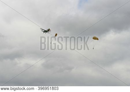Skydivers Jump From An Old Biplane Plane On A Cloudy Day