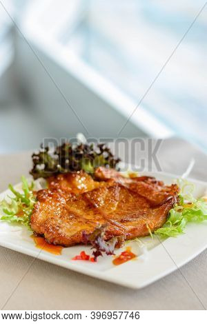 Main Course Of Pan-fried Pork Chop With Soy Sauce Served On Lettuce On A White Plate