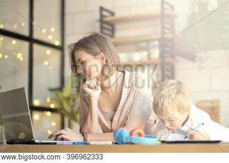 Mom Helping Young Son With Laptop To Do Homework. Young Woman Teaching Little Boy To Use The Compute