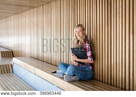 Side View Of Calm Adult University Student Girl Holding Copybooks With Faculty Or Lecture Notes, Loo