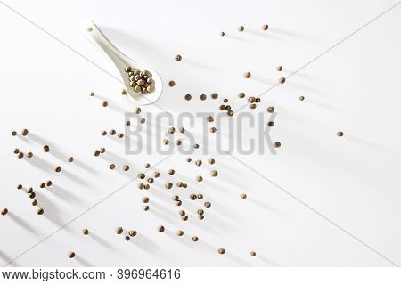 Jamaican Allspice Berries On White With Long Shadows. Jamaican Allspice Berries In A Spoon And A Bow