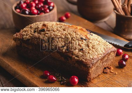 Loaf Of Cranberry Orange Bread With Bowl Of Cranberries In Background On Wooden Cutting Board