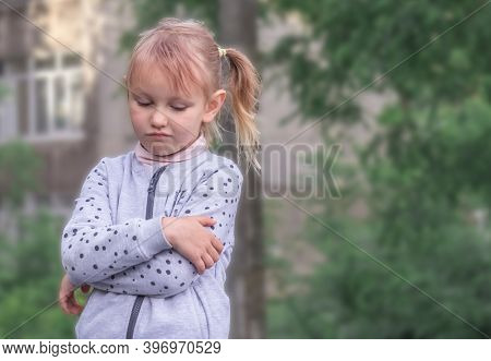 Girl 5 Years Old Blonde European Is Standing With Crossed Arms In The Park You Are Unhappy With Some