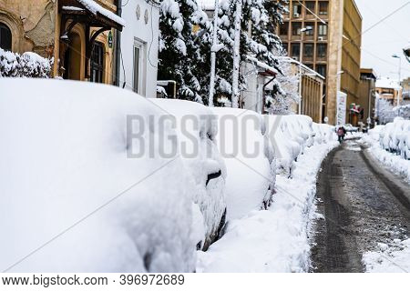 Cars Covered With Snow From The First Snow Fall Of The Year. Winter Concept, Snowy Cars Parked On Th