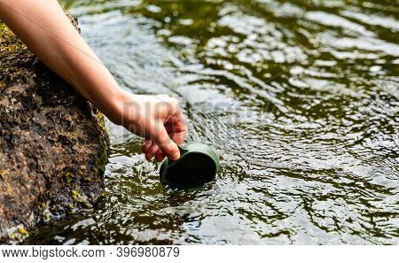 Hand Holding A Hikers Folding Cup, Reaching To The Surface Of Streaming Water To Fill The Cup.