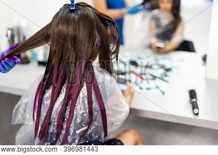 Hairdresser Dyes Hair For A Little Girl In A Hair Salon. Dyed, Bleached Hair