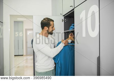 Male Doctor Standing Near The Locker And Holding His Uniform