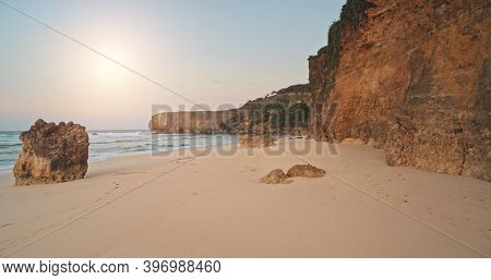 Sun light above sand beach at clean ocean bay water aerial. Cliff shore at sea gulf with stones, rocks. Soft sunlight at rocky coast of Sumba Island, Indonesia. Sunny paradise resort of Indonesia