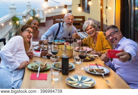 Happy Multiracial Senior Friends Having Fun Dining Together While Taking Selfie With Mobile Smartpho