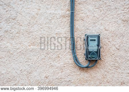 Electric Meter On White Concrete Wall. Power Meter