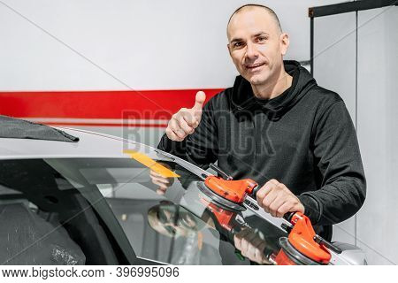 Automobile Technician Worker Replacing Windscreen Or Windshield Of A Car In Auto Service Station Gar