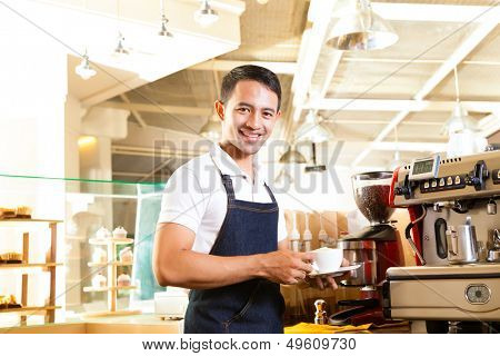 Coffeeshop - asian barista presents coffee in his shop