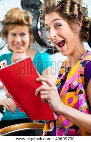 women at the hairdresser reading a magazine or a rag and chit-chat, while your hair drying under a hairdryer