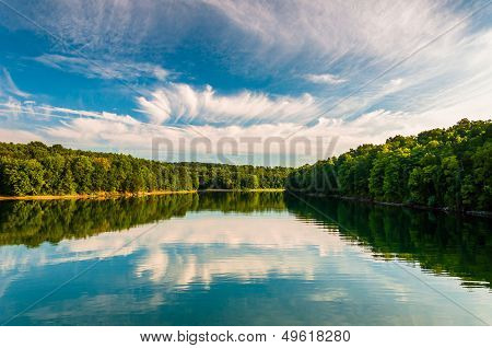 Evening reflections of clouds and trees in Lake Marburg Codorus State Park Pennsylvania. poster