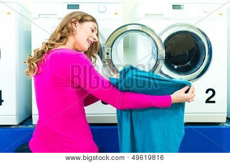 Woman in a launderette, washing her dirty laundry, in the background are washing machines, a female student is pleased about her clean blouse