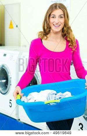 Young woman with laundry basket in a laundrette she washed their laundry clean and is happy about it