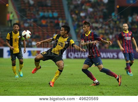 KUALA LUMPUR - AUGUST 10: Malaysia's WZ Haikal (25) defends FC Barcelona's Neymar (maroon/blue) attack in a game played at the Shah Alam Stadium on Aug 10, 2013 in Malaysia. FC Barcelona wins 3-1.