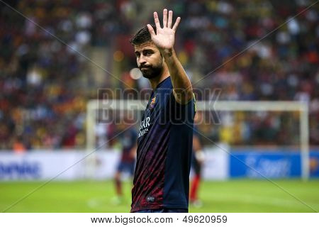 KUALA LUMPUR - AUGUST 10: FC Barcelona's player Gerard Pique waves to fans warm-up before the match against Malaysia at the Shah Alam Stadium on Aug 10, 2013 in Malaysia. FC Barcelona wins 3-1.