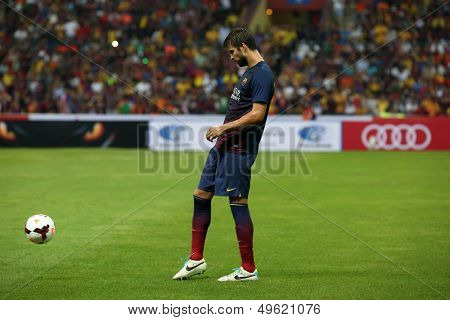 KUALA LUMPUR - AUGUST 10: FC Barcelona 's Gerard Pique kicks the ball during warm-up before the game against Malaysia at the Shah Alam Stadium on August 10, 2013 in Malaysia. FC Barcelona wins 3-1.