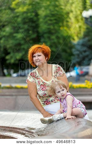 Family mother and daughter are sitting on the edge of a fountain in a city park poster